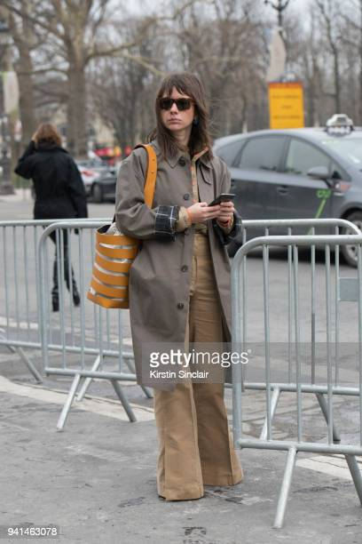 Fashion journalist Natasha Goldenberg wears a Vetements trenchcoat Paco Rabanne bag Céline trousers and sunglasses and a Patagonia top day 4 of Paris...