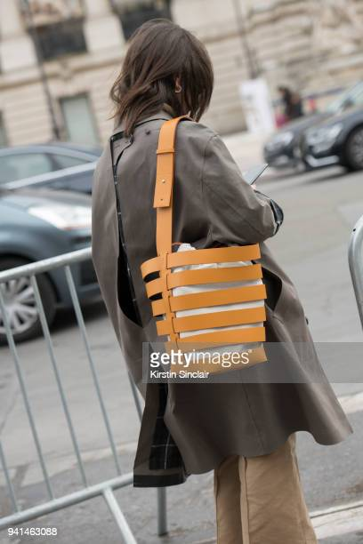 Fashion journalist Natasha Goldenberg wears a Vetements trenchcoat Celine trousers and a Paco Rabanne bag day 4 of Paris Womens Fashion Week...
