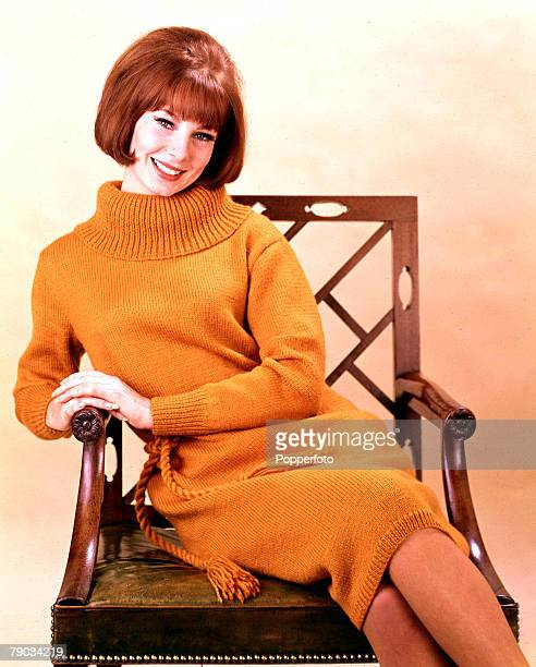 Smiling young woman wearing a soft orange knitted dress with a deep cowl rollneck sits comfortably in an antique chair