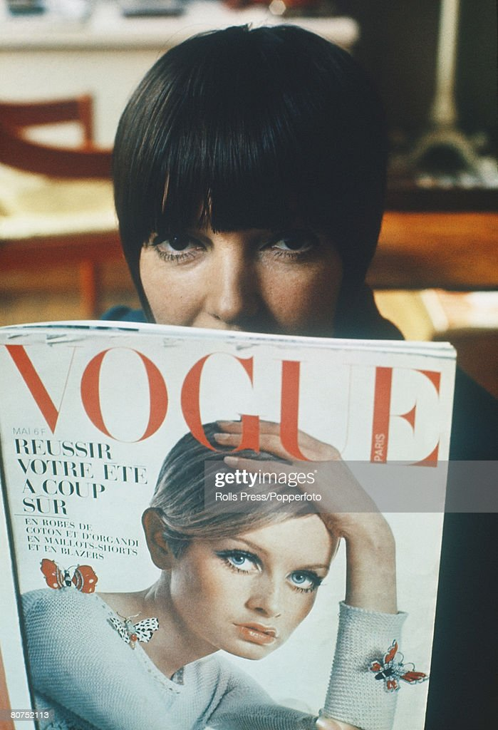 """Fashion 1967. London. Famous fashion designer Mary Quant reads a copy of """"Vogue"""" magazine, featuring Twiggy on the front cover, in her London boutique . : News Photo"""
