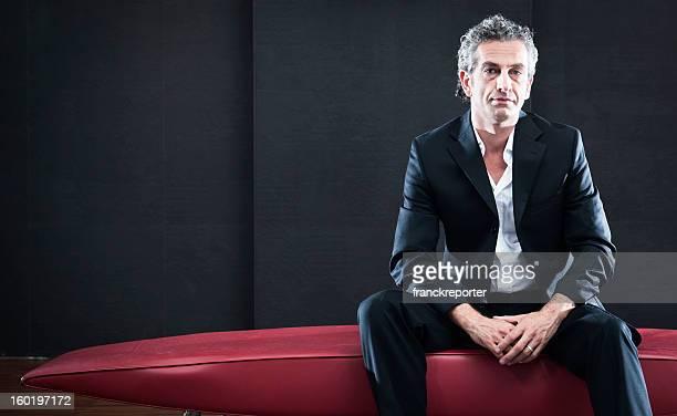 Mode Mann schaut die Kamera und posieren auf dem sofa