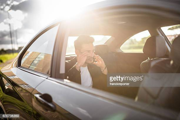 fashion man on the phone inside a car