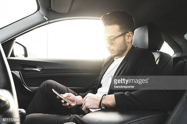 fashion man surfing with phone inside a car