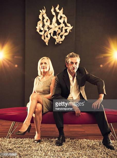 Fashion mature couple looking the camera and posing on sofa