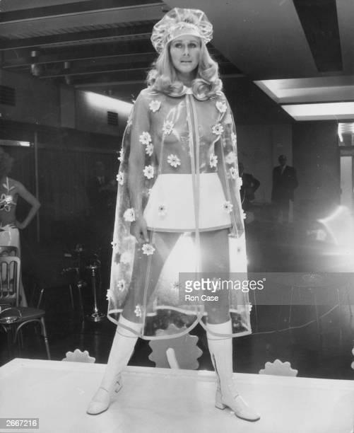 Fashion model Aldine Honey modelling the flower scattered long clear plastic rain cape from Berkertex Fashions
