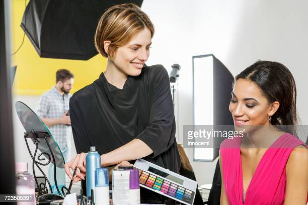 fashion model and make up artist in photography studio - visagist stockfoto's en -beelden