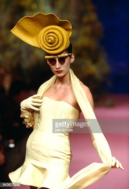Fashion model Anh Duong wears a yellow strapless haute couture cocktail dress and hat by Christian Lacroix at his springsummer 1988 fashion show in...
