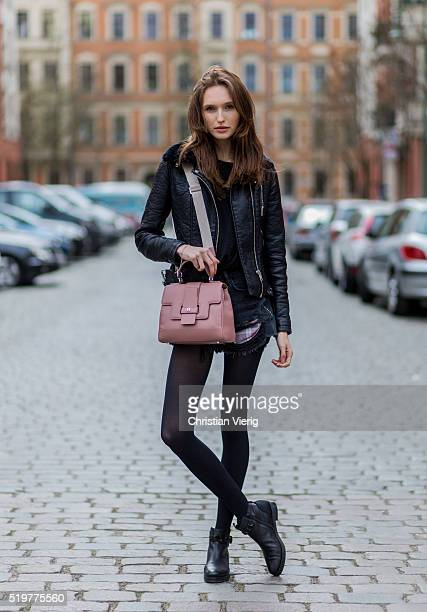 Fashion model Anna Wilken is wearing black denim jeans shorts and leather jacket from Zara a pink Aigner Munich bag and black Kennel Schemnger boots...