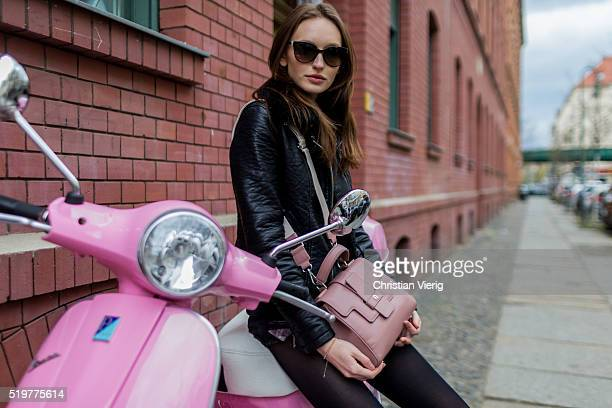 Fashion model Anna Wilken on a pink Vespa is wearing black denim jeans shorts and leather jacket from Zara a pink Aigner Munich bag on April 8 2016...