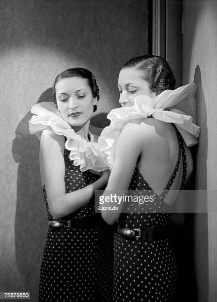 A fashion model appears with her reflection in a mirror as she wears a dress designed by French fashion designer Jeanne Lanvin that has a large...