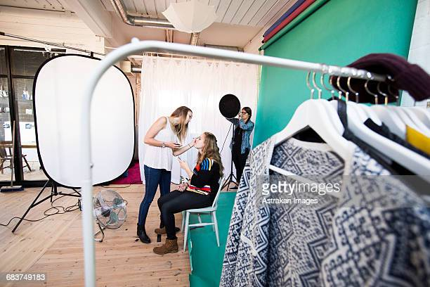 fashion model applying make-up to sister while assistant working in studio - fotosession stock-fotos und bilder