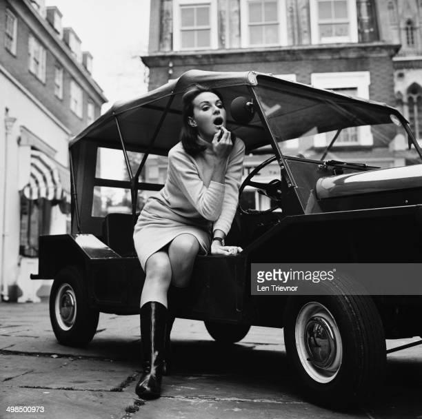 Fashion model Caroline Russell, the wife of Giles Montagu-Pollock, the 5th Baronet Montagu-Pollock, with an Austin Mini Moke, UK, 6th November 1964.