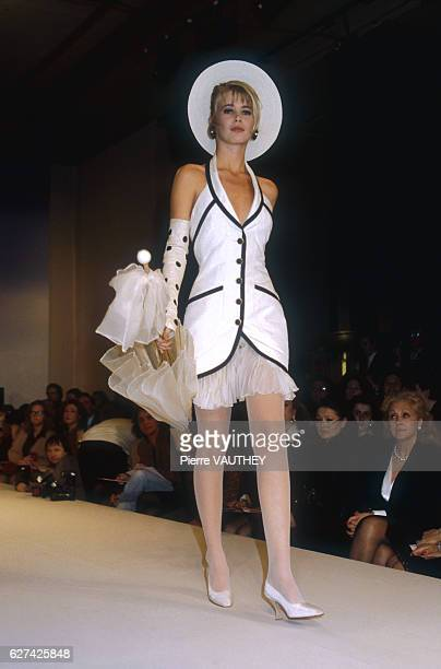 Fashion model Claudia Schiffer wears a white haute couture halter dress with black trim and a sheer skirt and brimmed hat by German fashion designer...