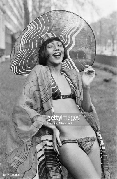 Fashion model Hazel wearing a bikini, a gown and a wide-brimmed hat in a matching fabric inspired by ripples in water, UK, 18th February 1974.