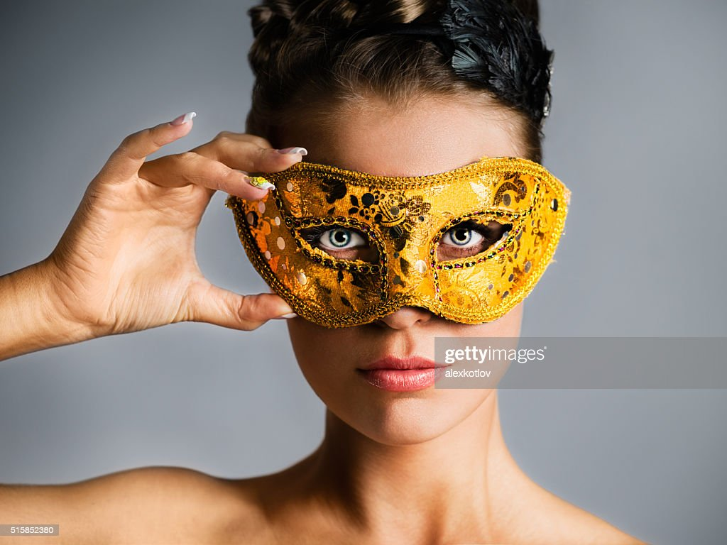 Fashion model hiding face behind golden mask : Stock Photo