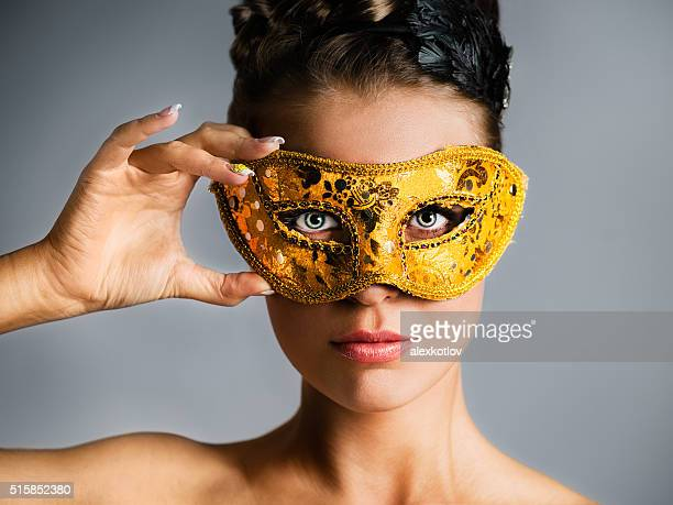 Fashion model hiding face behind golden mask