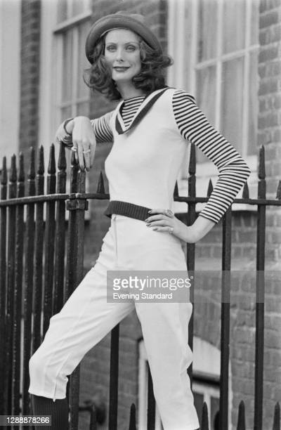 Fashion model in a white jumpsuit with striped sleeves and a hat, UK, October 1971.