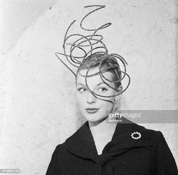 A fashion model in Paris wears a spiraling hat of fur covered wires designed by Franny Whitney an American socialite