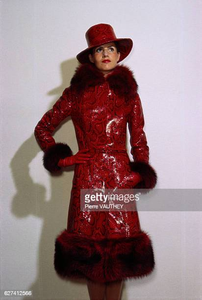 A fashion model in Paris wears readytowear women's fashions from the FallWinter 19731974 collection by French fashion house Givenchy She wears a red...