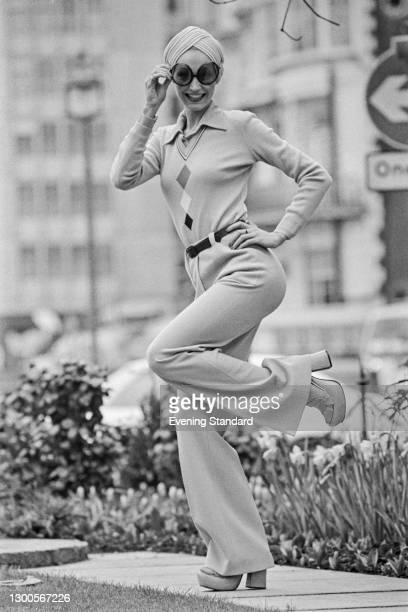 Fashion model Jay wearing a v-neck sweater, turban and flared trousers, UK, 29th March 1973.