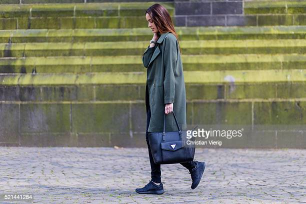 Fashion model Jueli Mery a green jacket from Forever 21, a black Topshop top, black denim jeans from Zara, black Nike sneaker and a black Guess bag...