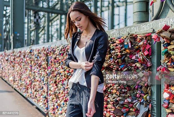 Fashion model Jueli Mery at Hohenzollernbruecke with love locks in the background wearing a black jogger pants and white top from Zara, black leather...