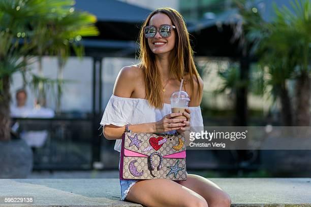 Fashion model Jueli Mery drinking Iced Coffe on a summer evening Jueli wearing white H&M off shoulder top, Gucci Dionysus bag, Zara denim shorts on...