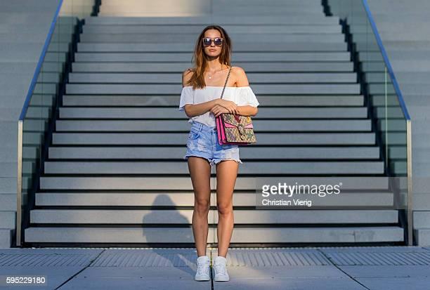 Fashion model Jueli Mery on a summer evening wearing white H&M off shoulder top, Gucci Dionysus bag, Zara denim shorts, white Michalsky sneaker on...