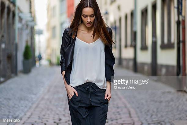 Fashion model Jueli Mery wearing a black jogger pants and white top from Zara, black leather jacket from Only April 14, 2016 in Cologne, Germany
