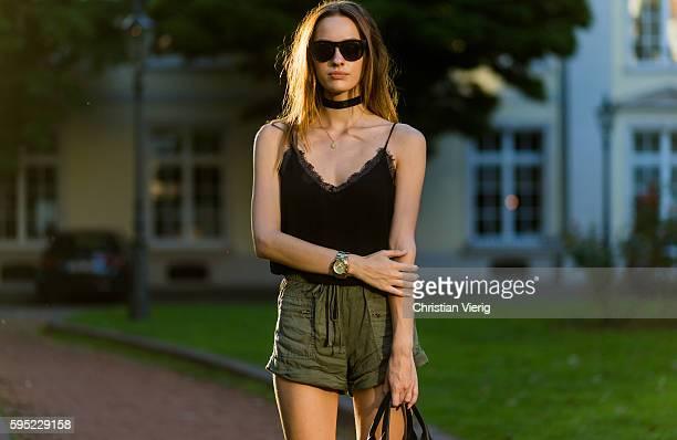 Fashion model Jueli Mery wearing a black Review top, black choker, black Versus Versace bag, olive Zara shorts, sunglasses, MK watch on August 25,...