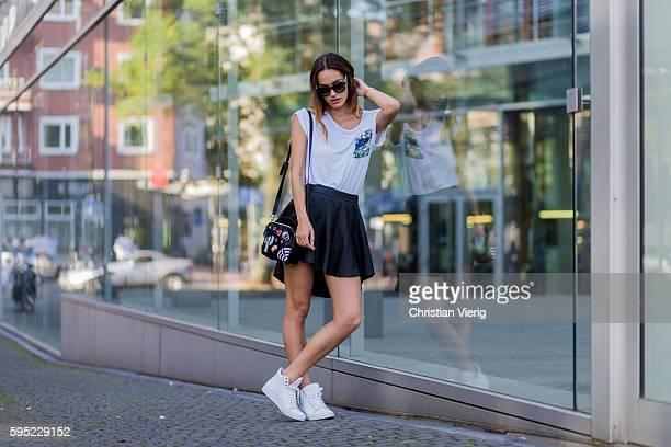 Fashion model Jueli Mery wearing a white Zara tshirt, black tigha mini skirt, black Zara bag, black Fendi sunglasses, white Michalsky sneaker, white...