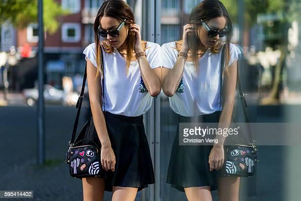 Fashion model Jueli Mery wearing a white Zara tshirt, black tigha mini skirt, black Zara bag, black Fendi sunglasses, white Michalsky sneaker on...