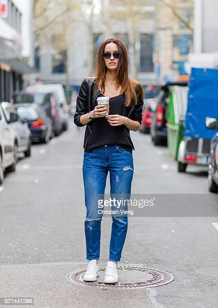 Fashion model Jueli Mery wearing black sunglasses, a black leather jacket from Only, top Distrikt, ripped denim jeans from Forever 21, white Adidas...