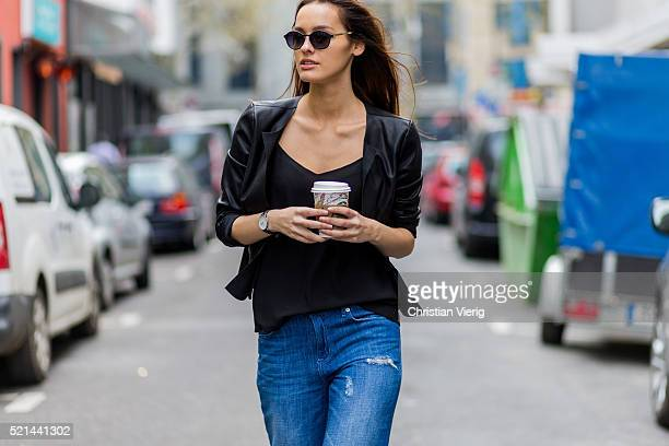 Fashion model Jueli Mery wearing black sunglasses, a black leather jacket from Only, top Distrikt, ripped denim jeans from Forever 21 while drinking...