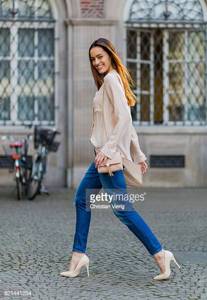 Fashion model Jueli Mery wearing blue ripped denim jeans from Forever 21, a nude button shirt from Costes, a Valentino mini bag and Zign pumps on...