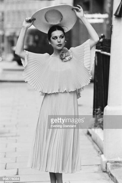 A fashion model lifting a floppy hat while wearing a plisse midi dress UK 25th January 1978
