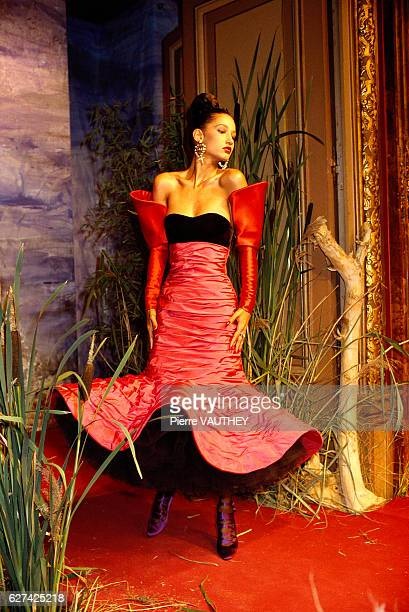 Fashion model Marpessa wears a pink and black flared haute couture dress and separated red sleeves by French fashion designer Christian Lacroix She...