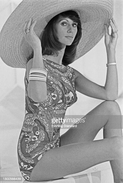 Fashion model Misty wearing a patterned swimsuit and a large straw hat, UK, 16th April 1973.