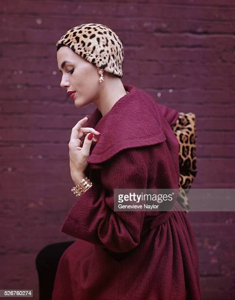 A fashion model poses in a plumcolored jacket and jaguar hat designed by Pauline Trigere