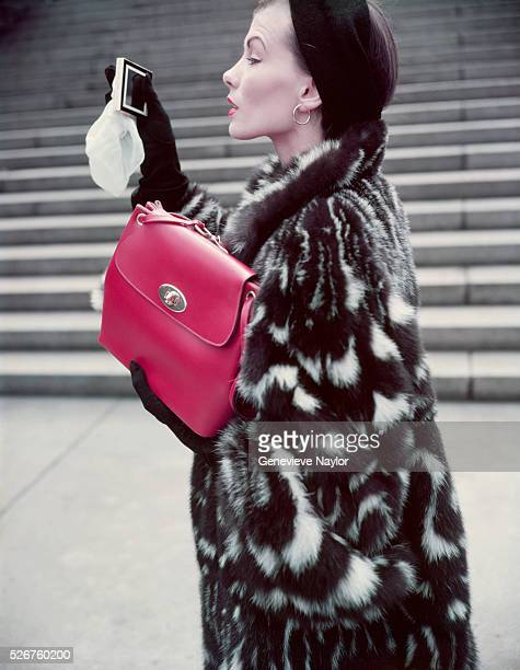 A fashion model poses in a skunk fur jacket designed by Christian Dior and holds a red calfskin handbag