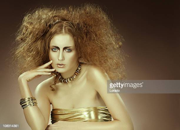 fashion model posing in gold - backcombed stock photos and pictures
