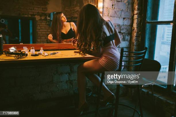fashion model sitting on stool in front of dressing table - dressing table stock photos and pictures