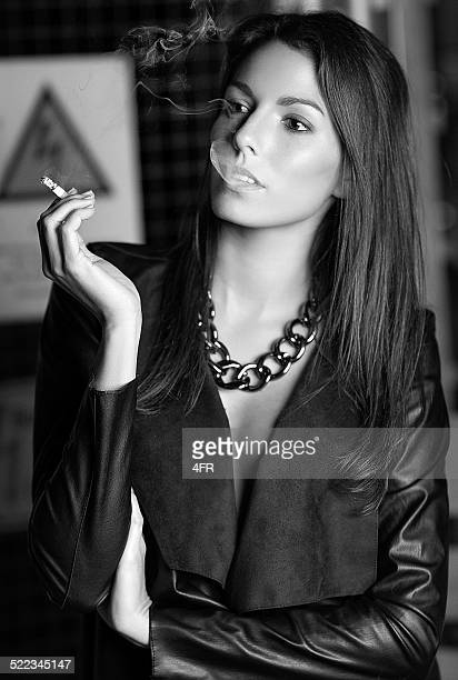 fashion model smoking in a warehouse - beautiful women smoking cigarettes stock photos and pictures