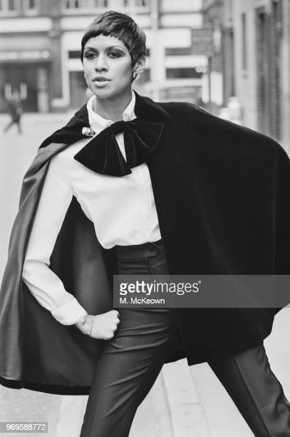 Fashion model Sonia Pugin wearing high waist trousers white shirt with black ribbon and cape UK 25th April 1967