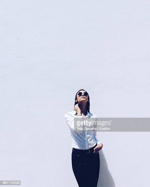 Fashion Model Standing Against White Wall