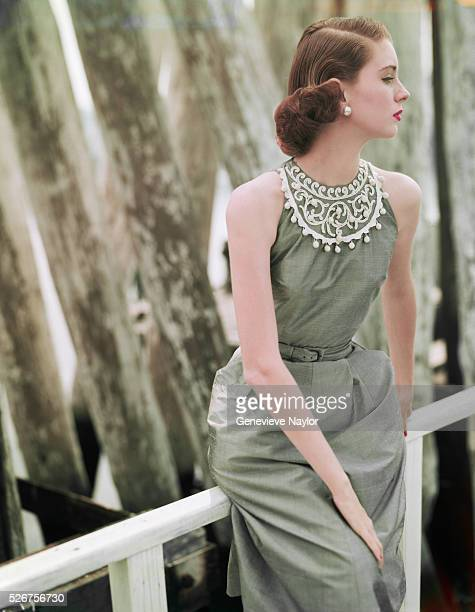 Fashion model Suzy Parker wears a light gray shantung dress by Cohama