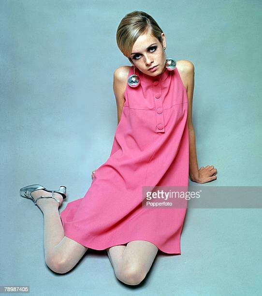 Fashion model Twiggy poses wearing a pink dress 1966