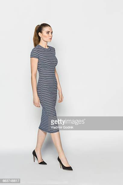 Fashion model walking against white background