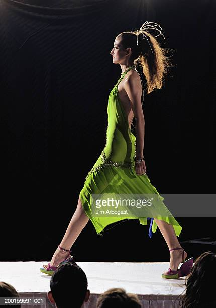 Fashion model walking on catwalk during fashion show, side view