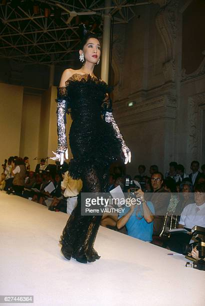 A fashion model wearing a black strapless haute couture evening gown by French fashion designer Emanuel Ungaro She is modeling the gown during his...
